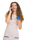 Happy young woman with credit card talking mobile phone Stock Image