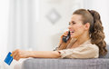 Happy young woman with credit card talking phone in living room Royalty Free Stock Photo