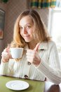Happy young woman with a cup of coffee in hand showing thumb up sign coffee break Royalty Free Stock Images