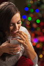 Happy young woman with cup of hot beverage eating marshmallow in front christmas lights Royalty Free Stock Photos