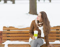 Happy young woman with cup of hot beverage enjoying winter long hair Royalty Free Stock Photo