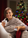 Happy young woman with cup of hot beverage near christmas tree watching tv Stock Images