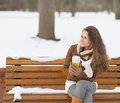 Happy young woman with cup of hot beverage sitting on bench and looking copy space Royalty Free Stock Image