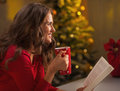 Happy young woman with cup of hot chocolate and book in kitchen christmas decorated Stock Photos