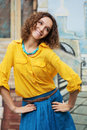 Happy young woman with curly hairs on the city street Stock Image