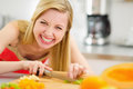 Happy young woman cutting fruits in kitchen pretty Royalty Free Stock Image