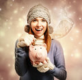 Happy young woman depositing money into her piggy bank Royalty Free Stock Photo