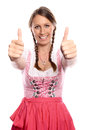 Happy young woman in a dirndl giving a thumbs up pinkish symbol for success and happiness oktoberfest concept isolated on white Stock Photography