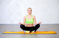 Happy young woman doing yoga exercises sitting in lotus position