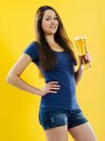 Happy young woman drinking beer photo of a beautiful brunette from a tall glass Stock Images