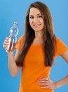Happy young woman drinking bottled water photo of a beautiful brunette over blue background Royalty Free Stock Photo