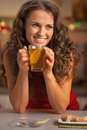 Happy young woman drinking ginger tea with lemon in kitchen Stock Photos