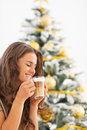 Happy young woman drinking latte macchiato near christmas tree in living room Stock Photos