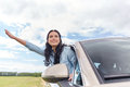 Happy young woman driving in car and waving hand Royalty Free Stock Photo