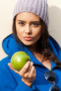 Happy young woman eating apple portrait of sexy near yellow wall and looking at camera diet dieting concept healthy food outdoors Royalty Free Stock Photo