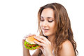 Happy young woman eating big yummy burger isolated on white background Royalty Free Stock Image