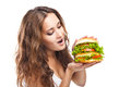 Happy young woman eating big yummy burger isolated on white background Stock Photo