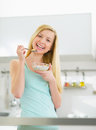 Happy young woman eating muesli in kitchen Royalty Free Stock Photo