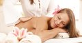 Happy young woman enjoying back massage with closed eyes smiling Stock Photography