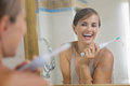 Happy young woman enjoying clean teeth after brushing electric brush Royalty Free Stock Photos
