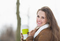 Happy young woman enjoying cup of hot beverage in winter park with long hair Stock Photo