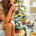 Young woman enjoying latte macchiato near christmas tree