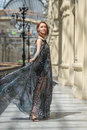Happy young woman in a fashionable flutter transparent cape pretty tender model is walking short black dress with at old fashioned Royalty Free Stock Photo
