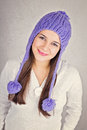 Happy young woman with fashionable purple beanie hat caucasian teenage girl smiling looking at camera against textured gray Stock Photography