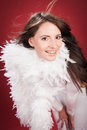 Happy young woman in feathery clothing close up with long hair wearing white while looking at the camera isolated on red Royalty Free Stock Photo
