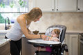 Happy young woman feeding cute little girl with a spoon. Royalty Free Stock Photo