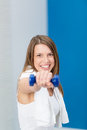 Happy young woman full of vitality working out at the gym with dumbbells in a health and fitness concept Royalty Free Stock Photo