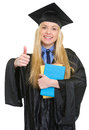 Happy young woman in graduation gown with books showing thumbs up Stock Photos