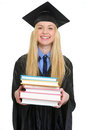Happy young woman in graduation gown giving books isolated on white Royalty Free Stock Image