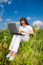 Happy Young Woman on the grass field with a laptop Stock Photo