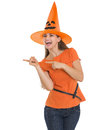 Happy young woman in Halloween hat pointing side Stock Photography