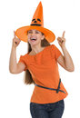 Happy young woman in Halloween hat pointing up Royalty Free Stock Images