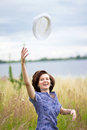 Happy young woman with hat in air Royalty Free Stock Photography