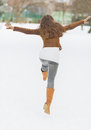 Happy young woman having fun in winter park rear view with long hair Royalty Free Stock Photos
