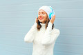 Happy young woman in headphones enjoys listens to music wearing a knitted hat, sweater over blue