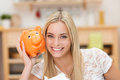 Happy young woman with her piggy bank cute orange holding it to cheek as she smiles broadly at the camera Royalty Free Stock Photography