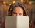 Happy young woman hiding behind book in christmas decorated kitchen Stock Image