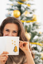 Happy young woman hiding behind christmas postcard in living room Stock Image