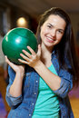 Happy young woman holding ball in bowling club Royalty Free Stock Photo