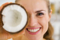 Happy young woman holding coconut piece in front of eye high resolution photo Royalty Free Stock Photography
