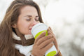 Happy young woman holding cup of hot beverage in winter outdoors with long hair Royalty Free Stock Photo