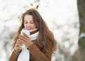 Happy young woman holding cup of hot beverage in winter park with long hair Stock Photos
