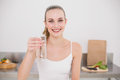 Happy young woman holding glass of water in the kitchen at home Royalty Free Stock Images