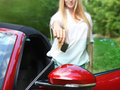 Happy young woman holding keys to her cabrio blond sport car Stock Images