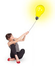 Happy young woman holding light bulb balloon Royalty Free Stock Photography