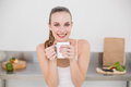Happy young woman holding mug in the kitchen at home Royalty Free Stock Photos